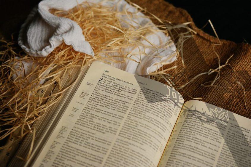 Pismo Święte otworzone na ewangelii św. Łukasza, leżące na sianie.