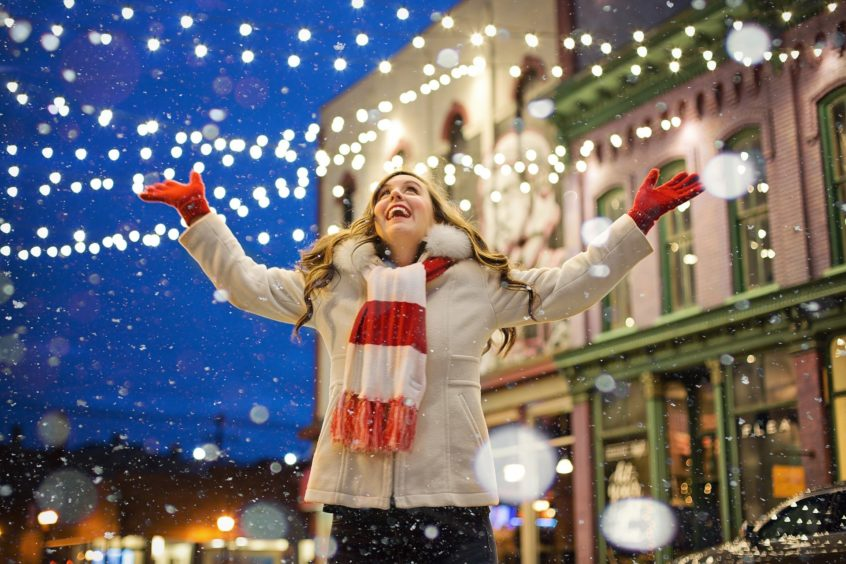 Kobieta z radością spoglądająca w niebo na spadający śnieg.